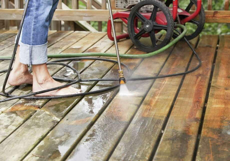 Use a pressure washer to freshen a weathered deck. Photo: Getty Images / (c) BanksPhotos