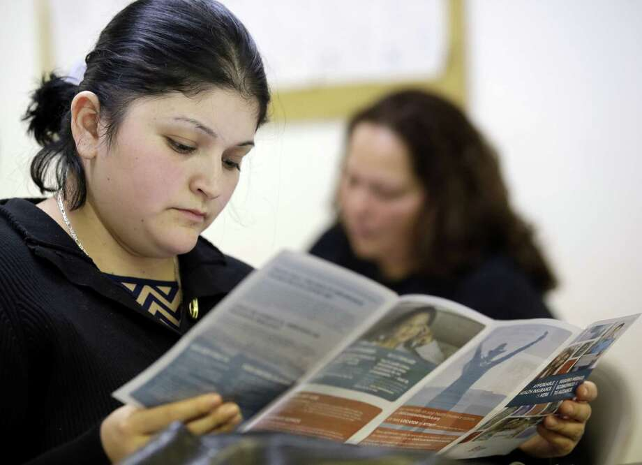 Sara Rodriguez looks over an Affordable Care Act brochure March 11 in Houston. Rodriguez, like others who listened to a presentation on the ACA, says she can't afford insurance, even for $50 a month. Photo: Associated Press / AP