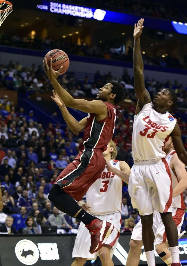Stanford Cardinal guard Chasson Randle (5) lays the ball up past New Mexico Lobos guard Deshawn Delaney (33) in the second half during the 2nd round of the 2014 NCAA Men's  Basketball Championship at Scottrade Center. Photo: Scott Rovak, Reuters