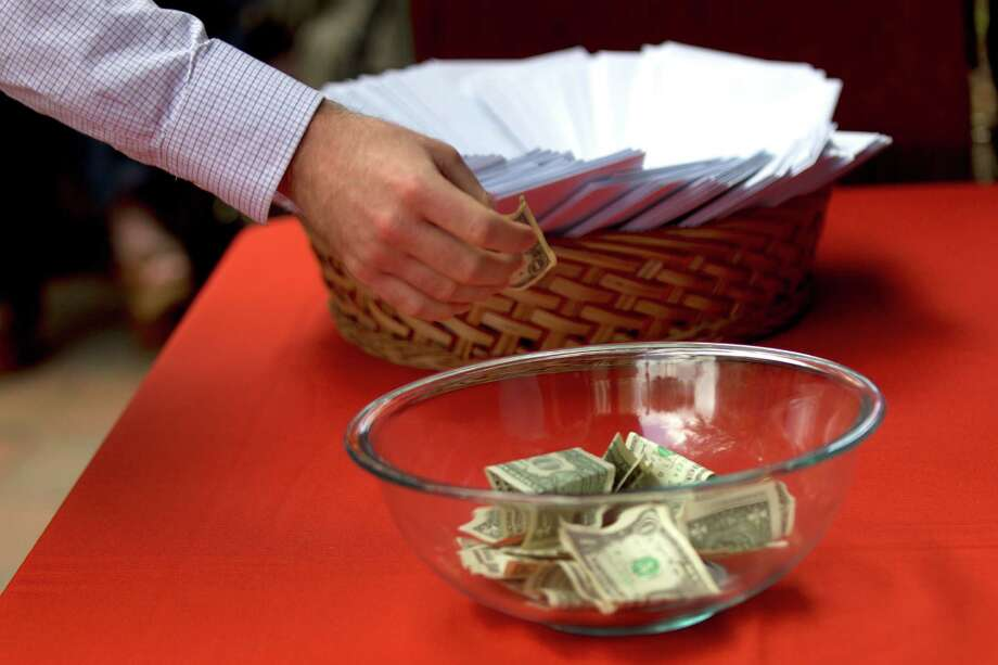 A medical student drops a dollar in a bowl during Match Day festivities at the University of Texas Health Science Center Medical School Friday, March 21, 2014, in Houston. The students are called for their matches randomly and the final name called wins the bowl of cash. Photo: Brett Coomer, Houston Chronicle / © 2014 Houston Chronicle