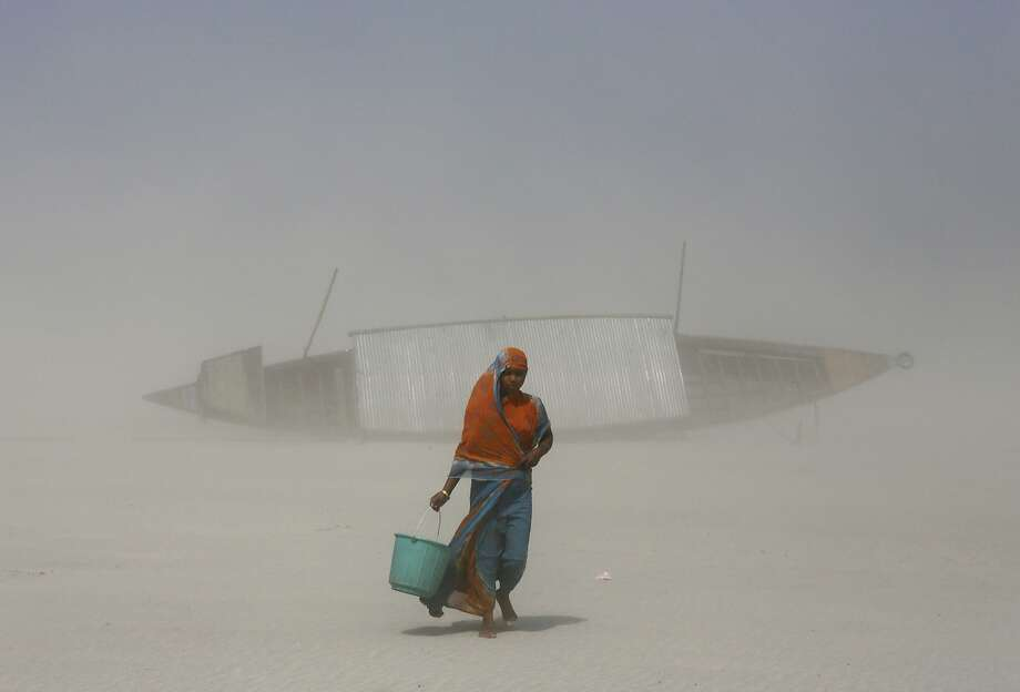 Buffeted by blowing sand,an Indian woman makes her way back to her village after filling a 