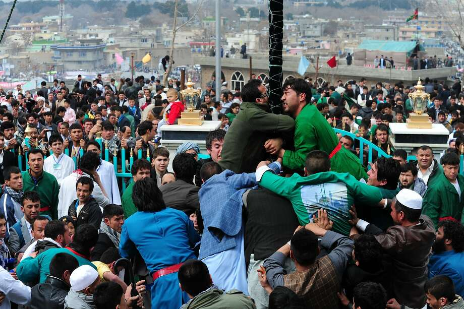 Pole kissers:During Nowruz (New Year's) festivities in Kabul, Afghan men wrestle each other to reach the holy mace in front of the Sakhi 