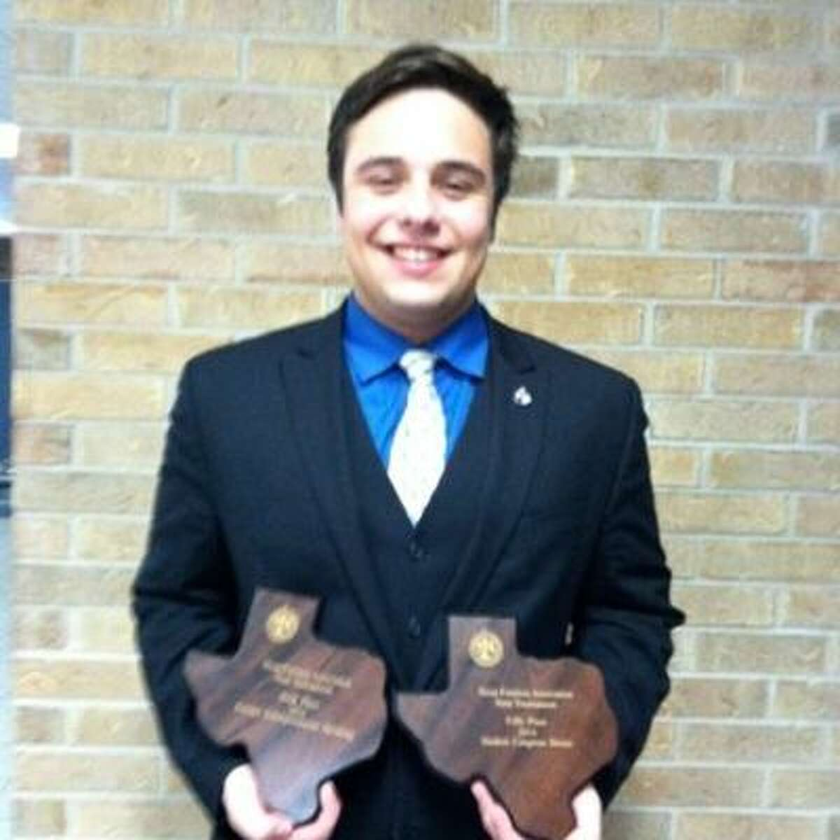 Dylan Dickens holds awards he earned in the Texas Forensic Association State Meet.