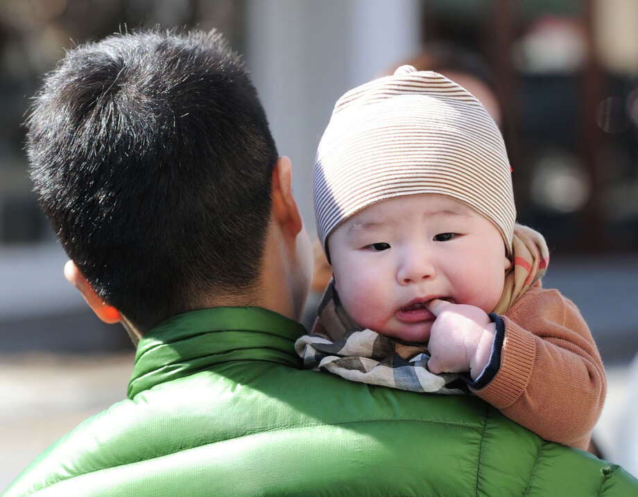 Frank Alexander Park, 6-months-old, nibbles on his finger while being carried by his father, Frank Spencer Park of New York City, while the pair were enjoying the day strolling on Greenwich Avenue in the sunny and mild spring weather in Greenwich, Conn., Friday afternoon, March 21, 2014. Photo: Bob Luckey / Greenwich Time