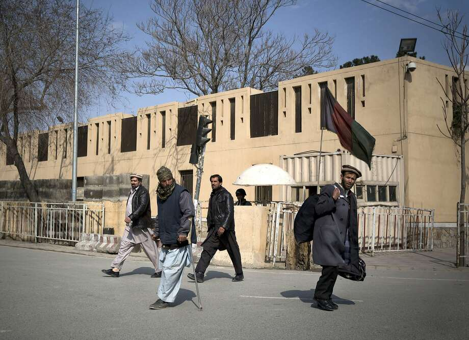 Afghans walk by the Serena Hotel in downtown Kabul, a day after four men hiding guns in their shoes slipped by security to attack the hotel's restaurant. Photo: Anja Niedringhaus, Associated Press
