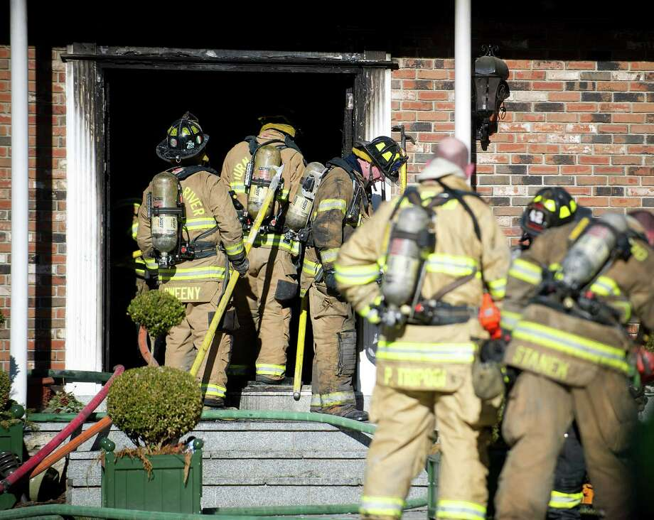 Firefighters extinguish a fire inside the home at 449 Westover Road in Stamford, Conn., on March 21, 2014. Photo: Lindsay Perry / Stamford Advocate