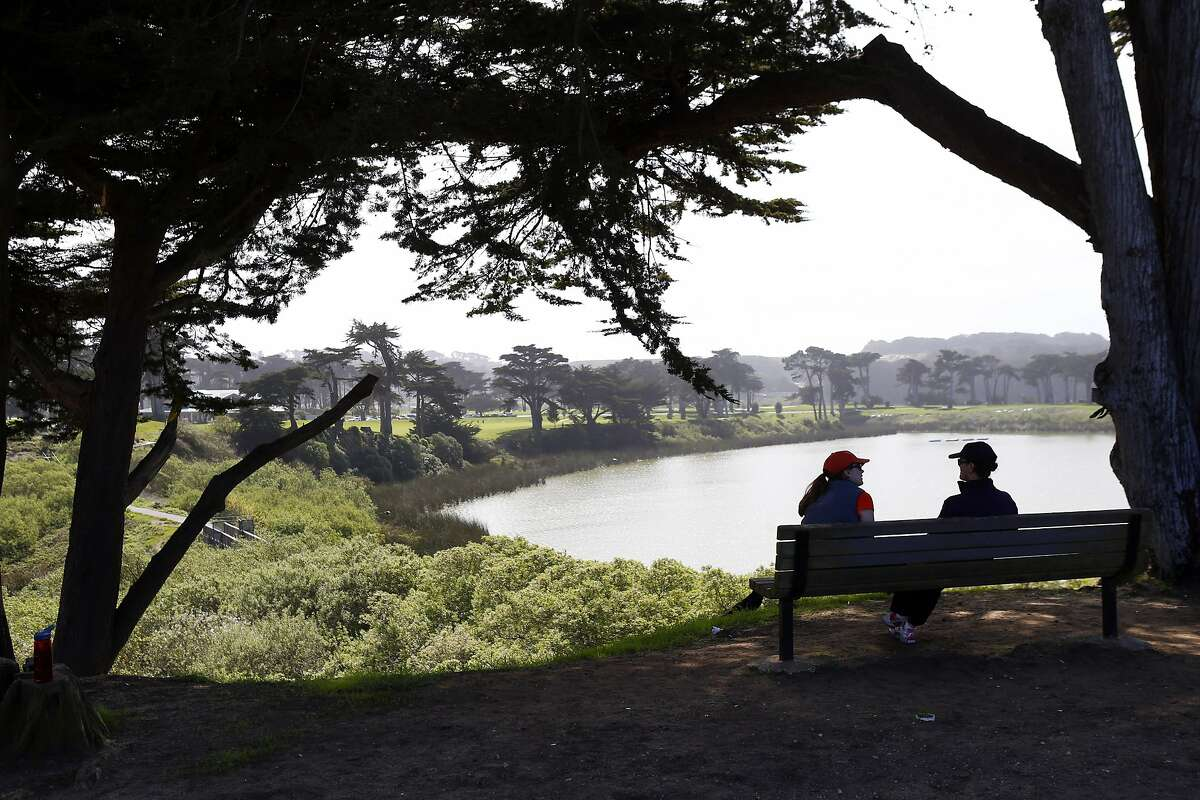 Two park visitors sit on a bench overlooking Lake Merced in San Francisco, Calif., on Thursday, March 20, 2014, where park critters now include coyotes. City parks staff are getting training on how to deal with coyotes, which are increasingly making their presence known in city parks.