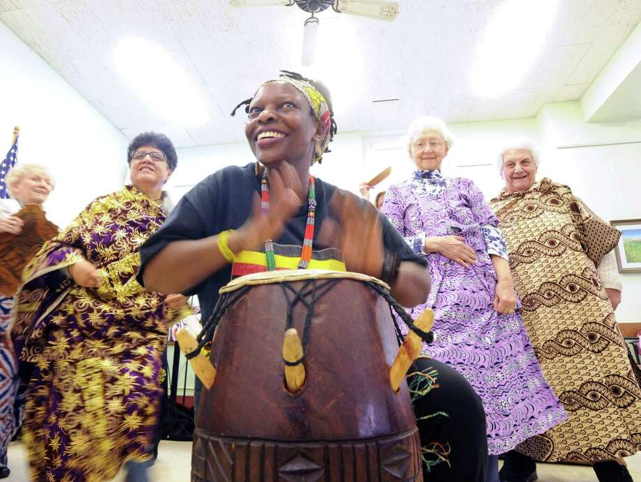 African Cultural Expert, Rita Kabli Wagener, plays an African drum during a performance and talk she gave about African and Ugandan culture to a small group of seniors at the Greenwich Senior Center in Greenwich Conn., Friday afternoon, March 21, 2014. In the background wearing tradtional African clothing for women are a group of Greenwich seniors who attended Wagener's show and tried on the African clothing Wagener brought. Wagener said she is a native of Uganda in Africa and that she hails from the Baganda People. Photo: Bob Luckey / Greenwich Time