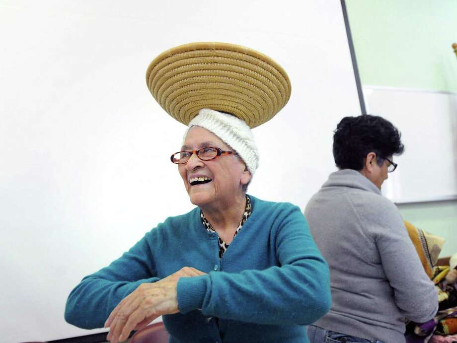 Lidia Calderon, a member of the Greenwich Senior Center, attempts to walk while balancing an African basket bowl on her head during a visit to the center by African Cultural Expert, Rita Kabli Wagener, who put on an African drumming performance and gave a talk about African and Ugandan culture to a small group of seniors at the Greenwich Senior Center in Greenwich Conn., Friday afternoon, March 21, 2014. Photo: Bob Luckey / Greenwich Time