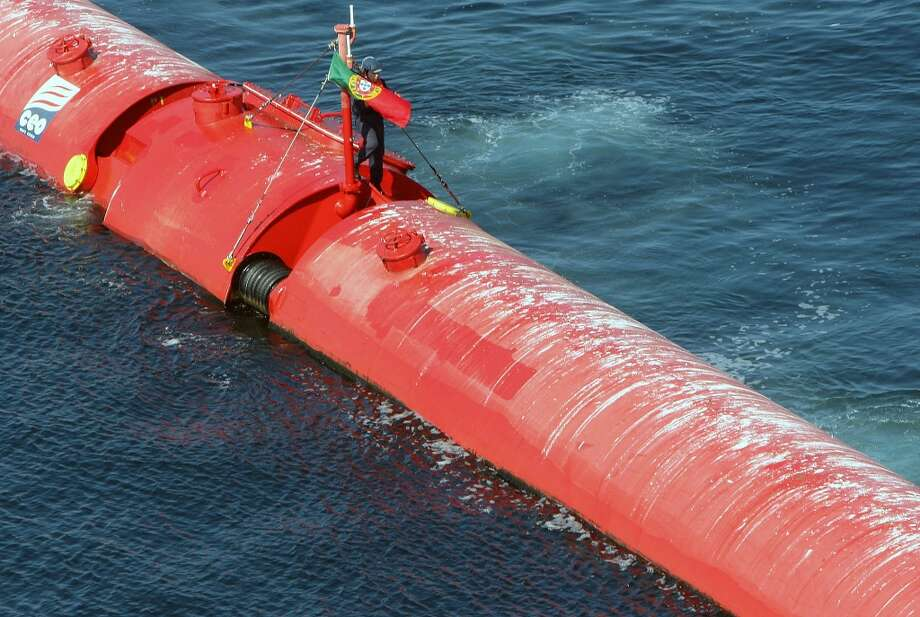 A worker ties a Portuguese flag to an off-shore electricity generator based on wave power off of Portugalís Atlantic coast near the northern town of Povoa de Varzim in September 2008. Portugal inaugurated a wave energy farm that uses floating tubes whose bobbing motion pumps hydraulic fluid to drive generators. Photo: JOAO ABREU MIRANDA, AFP/Getty Images