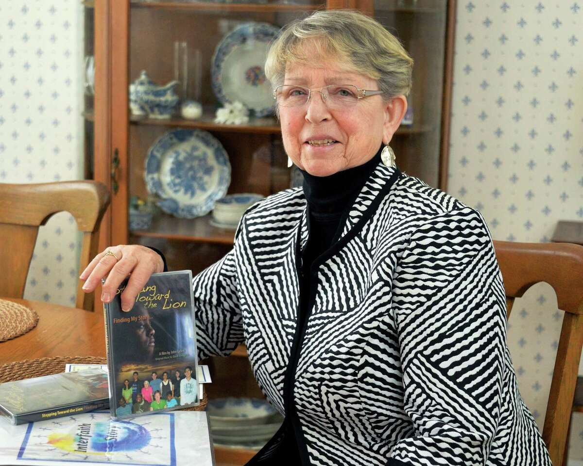 """Educator and storyteller Gert Johnson with DVD's of the upcoming film """"Stepping Toward the Lion"""" by John Lyden, an alum of Children at the Well, in her home Wednesday March 19, 2014, in Niskayuna, NY. (John Carl D'Annibale / Times Union)"""