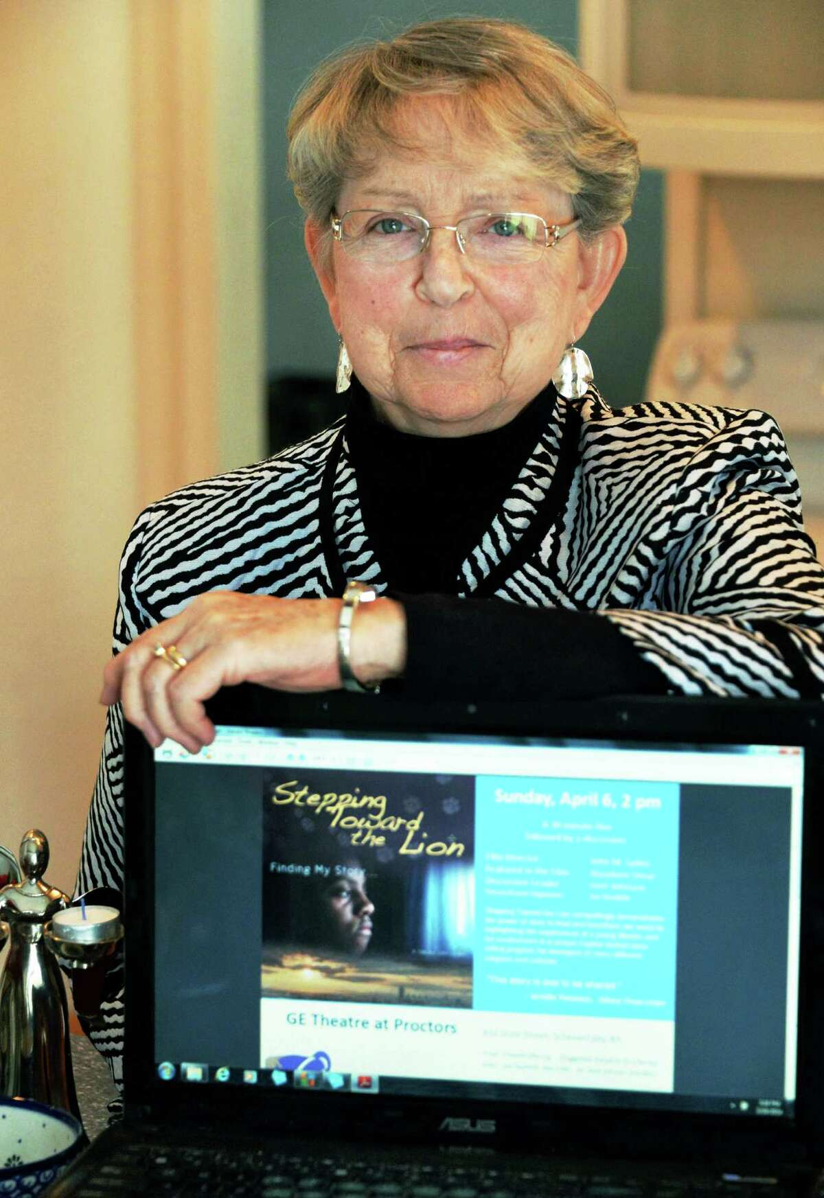 """Educator and storyteller Gert Johnson with website for the upcoming film """"Stepping Toward the Lion"""" by John Lyden, an alum of Children at the Well, in her home Wednesday March 19, 2014, in Niskayuna, NY. (John Carl D'Annibale / Times Union)"""