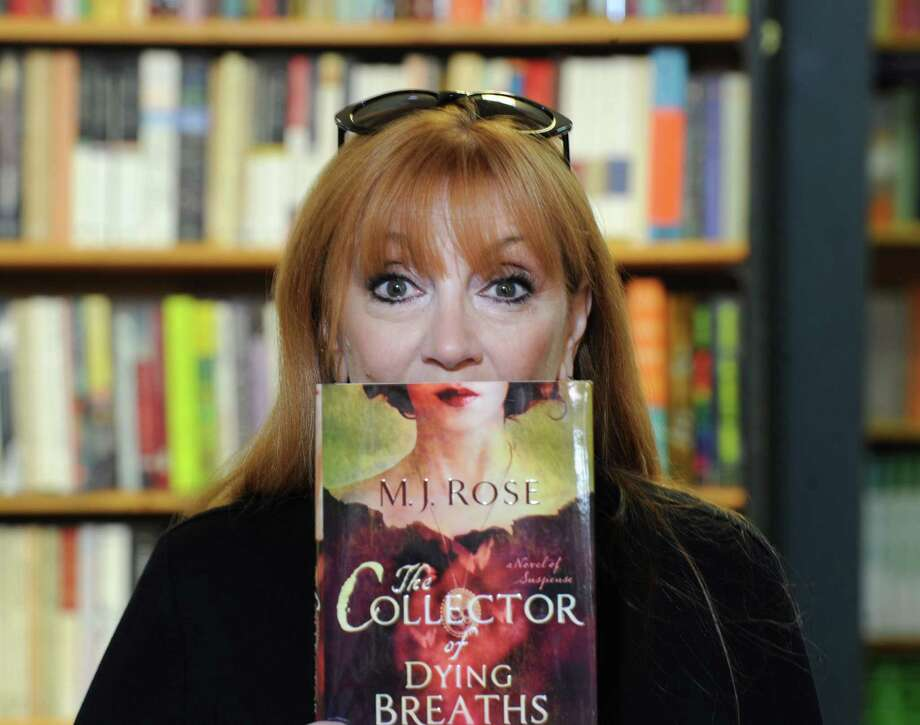 "Greenwich resident M.J. Rose holds her new novel ""The Collector of Dying Breaths,"" at Diane's Books in Greenwich, Conn., Friday, March 21, 2014. Photo: Bob Luckey / Greenwich Time"