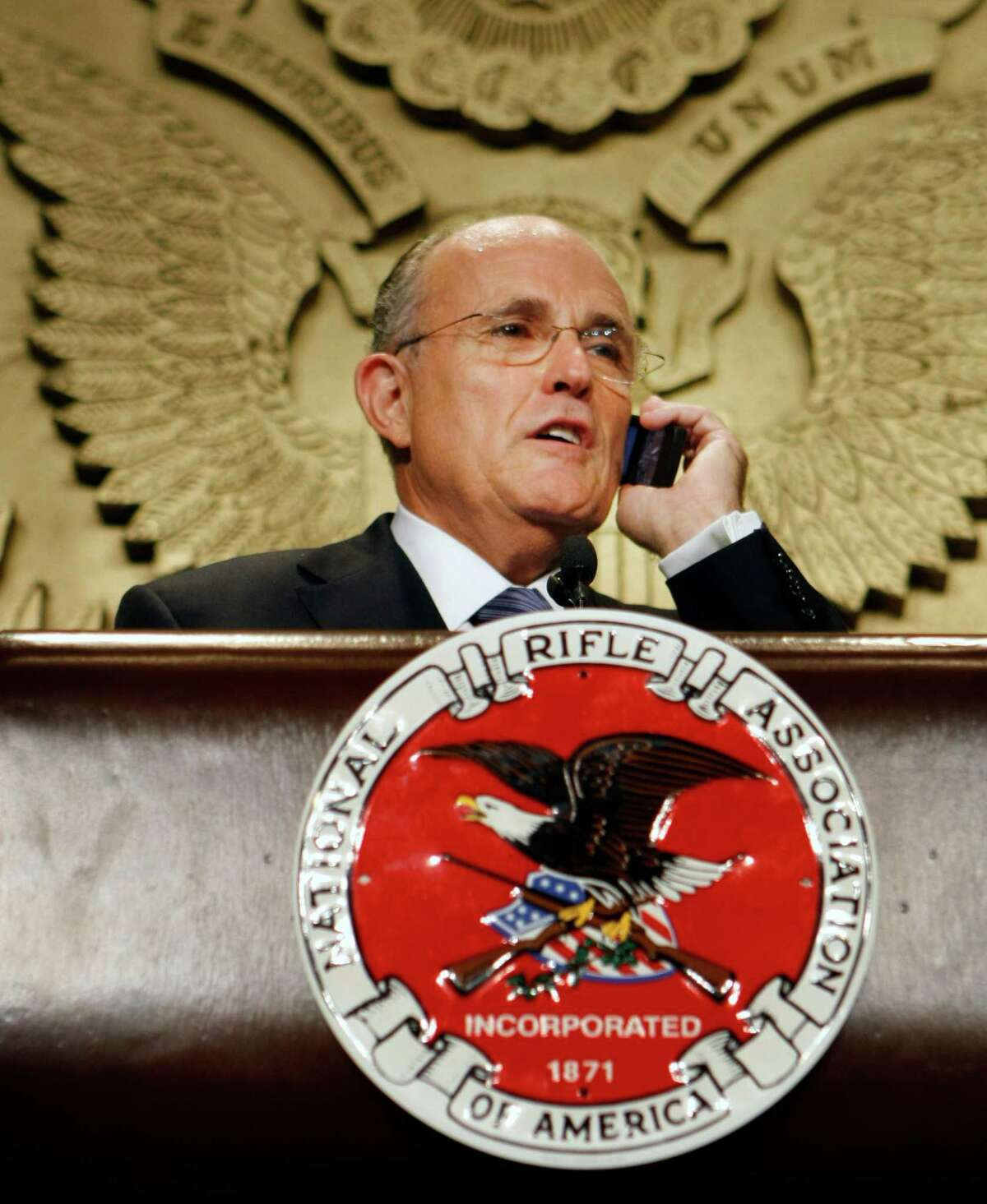 Former New York Mayor Rudy Giuliani takes a cell phone call, he said was from his wife, while delivering remarks to the National Rifle Association in Washington, Friday, Sept. 21, 2007.