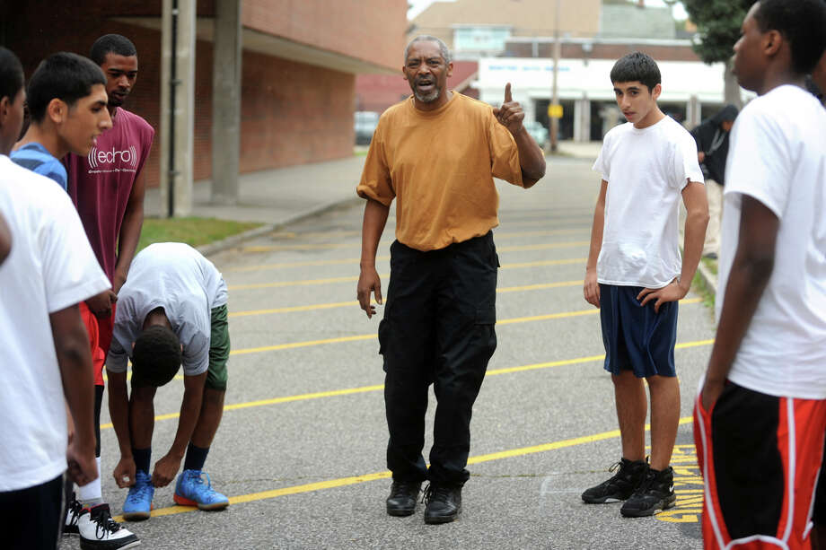 Coach Bernie Lofton speaks to his cross county team during practice in an alley on the campus of Bassick High School, in Bridgeport, Conn. Oct. 12th, 2012. Lofton also attended Bassick, and currently works as a security gurad at the school Photo: Ned Gerard / Connecticut Post
