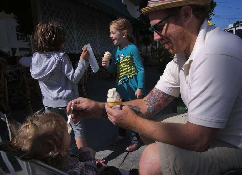 Dagan Ministero (right), Lillian Ministero (center) and Sunny Ministero (stroller) eat ice cream in the sun. Photo: Andre Zandona, The Chronicle