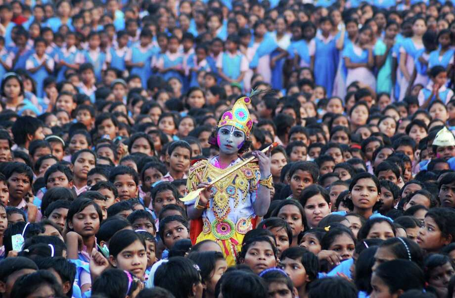 An Indian schoolchild dressed as the Hindu god Krishna and adorned with colored powder stands among other students during celebrations for the spring festival Holi in Bhubaneswar. Photo: Asit Kumar / AFP / Getty Images / AFP