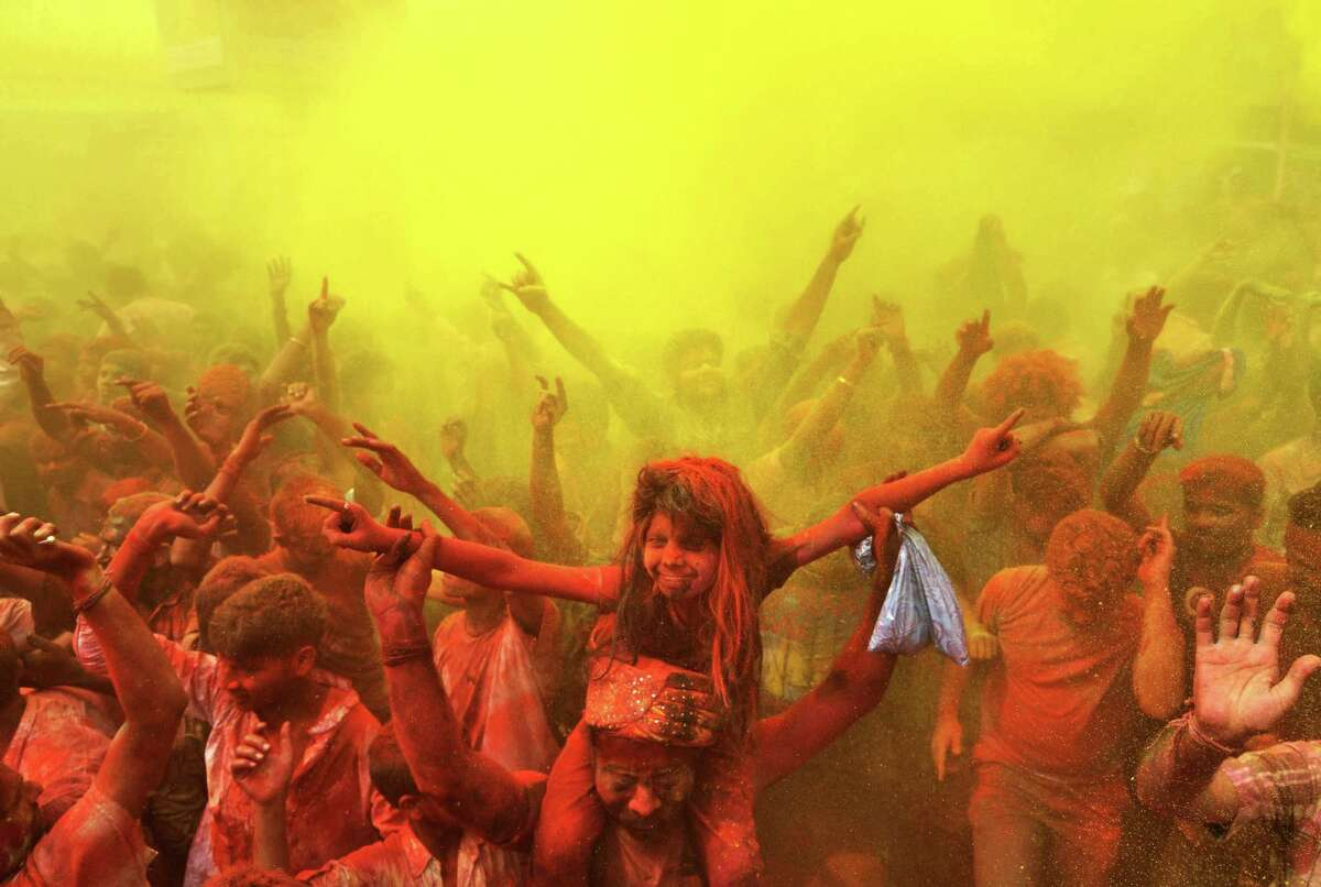 Indian revelers cover each other with colored powder and dance while taking part in Holi festival celebrations in Guwahati.