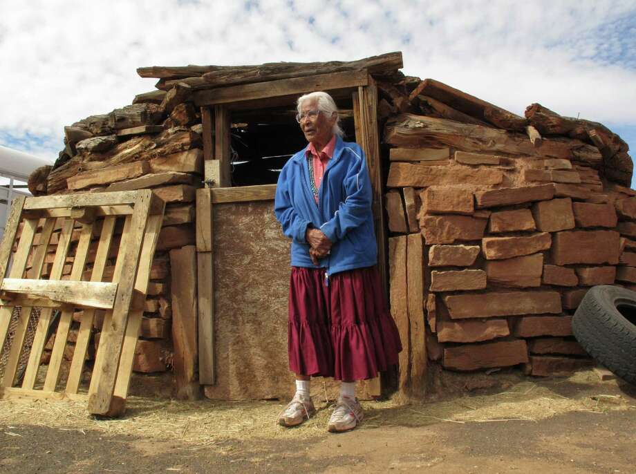 Navajo elder Stella Peshlakai Smith stands outside a traditional dwelling on her homestead at Wupatki National Monument in northern Arizona. Photo: Photos By Felicia Fonseca / Associated Press / AP