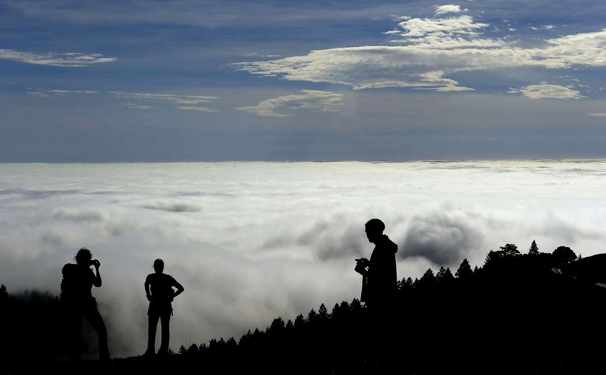 Jessica O'Brien, (left) from Seattle , Brenda Fromolz , from Wisconsin and Lenny Cavaluzzi from Walnut Creek enjoy the view of a huge fog bank rolling into San Francisco Bay while atop Mt. Tamalpais in Marin County on Tuesday Feb. 11, 2014.