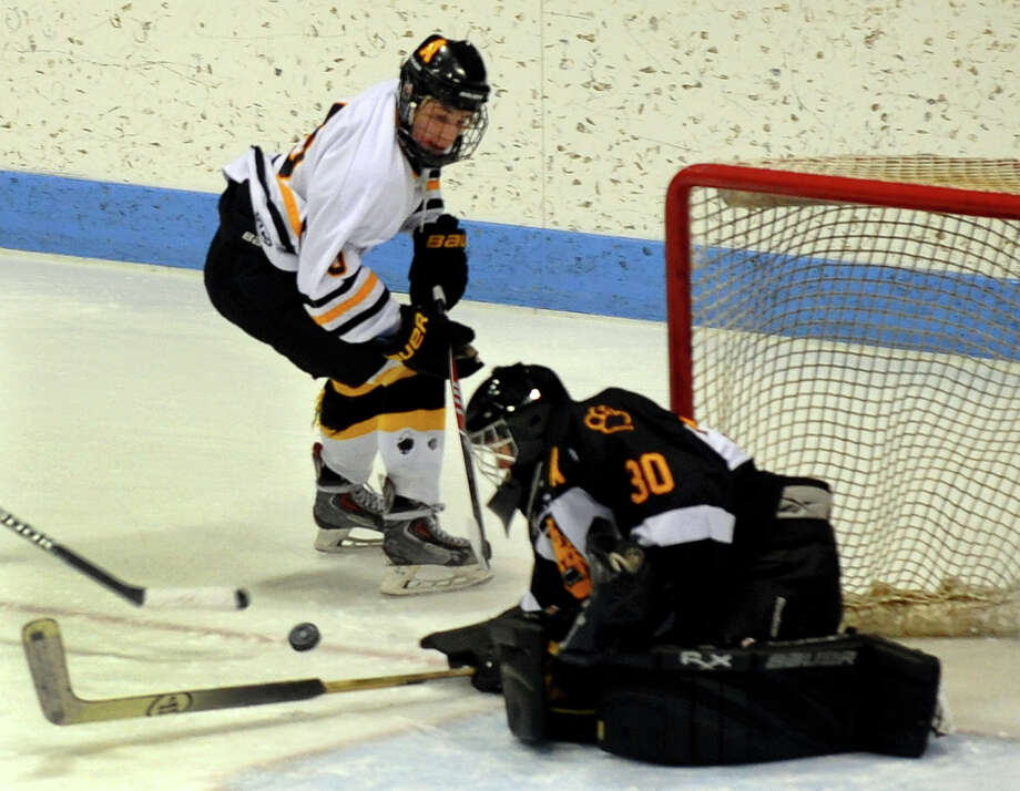 A shot by Amity's Adam Shea is deflected by Daniel Hand goalie Chase Briggs, during Div. II state boys hockey final action at Ingalls Rink in New Haven, Conn. on Friday March 21, 2014. Photo: Christian Abraham / Connecticut Post