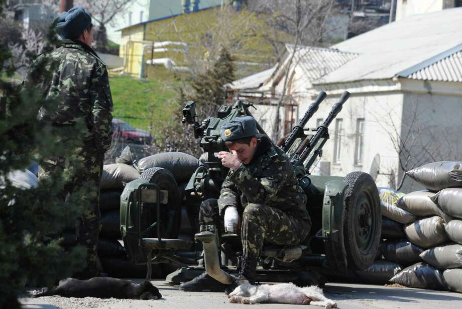 A Ukrainian army soldier smokes a cigarette next to a machine gun at the Belbek air force base not far from the city of Sevastopol, in Crimea, on March 21, 2014. Surly and dejected, many Ukrainian soldiers at the Perevalne base in Crimea deserted their posts today, crossing groups of buoyant Russian soldiers moving in -- but 200 were said to be resisting. Overwhelmed by superior force and on the day Russia formally claimed the Black Sea peninsula as its territory, the biggest base still holding out against a creeping month-long invasion was slowly giving up. AFP PHOTO / VIKTOR DRACHEVVIKTOR DRACHEV/AFP/Getty Images ORG XMIT: - Photo: VIKTOR DRACHEV / AFP