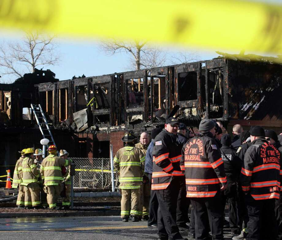 Firefighters investigate a fire at the Mariner's Cove Hotel, where residents included Superstorm Sandy victims, in Point Pleasant Beach, N.J. Photo: David Gard / Associated Press / FR158623 AP
