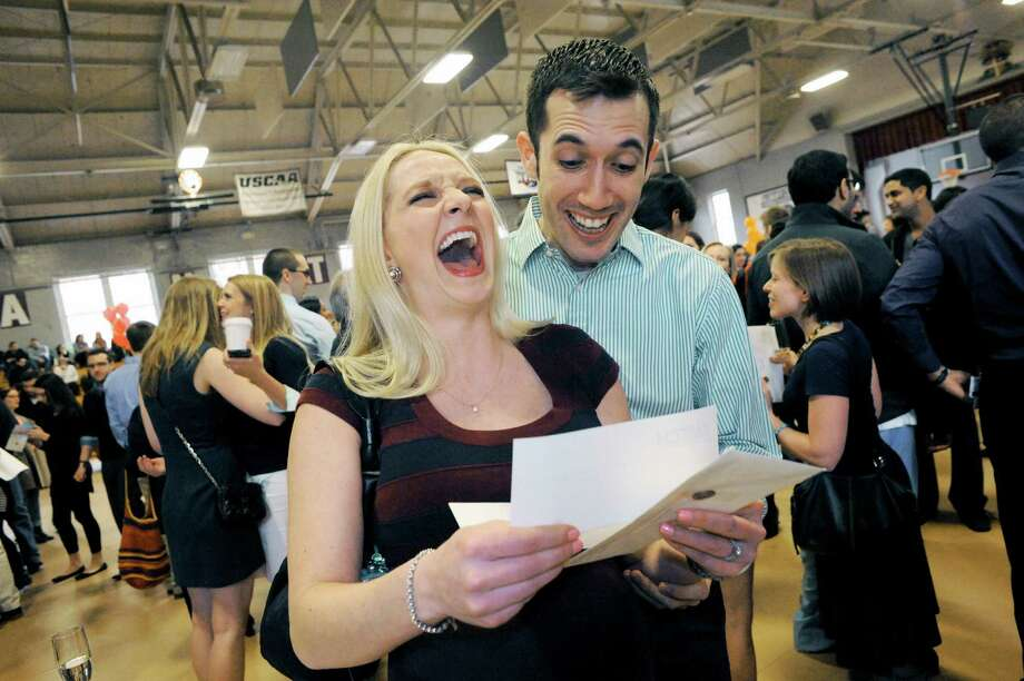 Graduating medical student Lara Reichert, maiden name Kostun, with her husband William Reichert reacts after opening her placement letter during Albany Medical College's Match Day Friday, March 21, 2014, in Albany, N.Y. Match Day is when graduating medical school students find out where they will complete their medical training in a residency program. Students make several picks, and then the corresponding chosen hospitals select which students they will take in there program. (Michael P. Farrell/Times Union) Photo: Michael P. Farrell / 00026097A