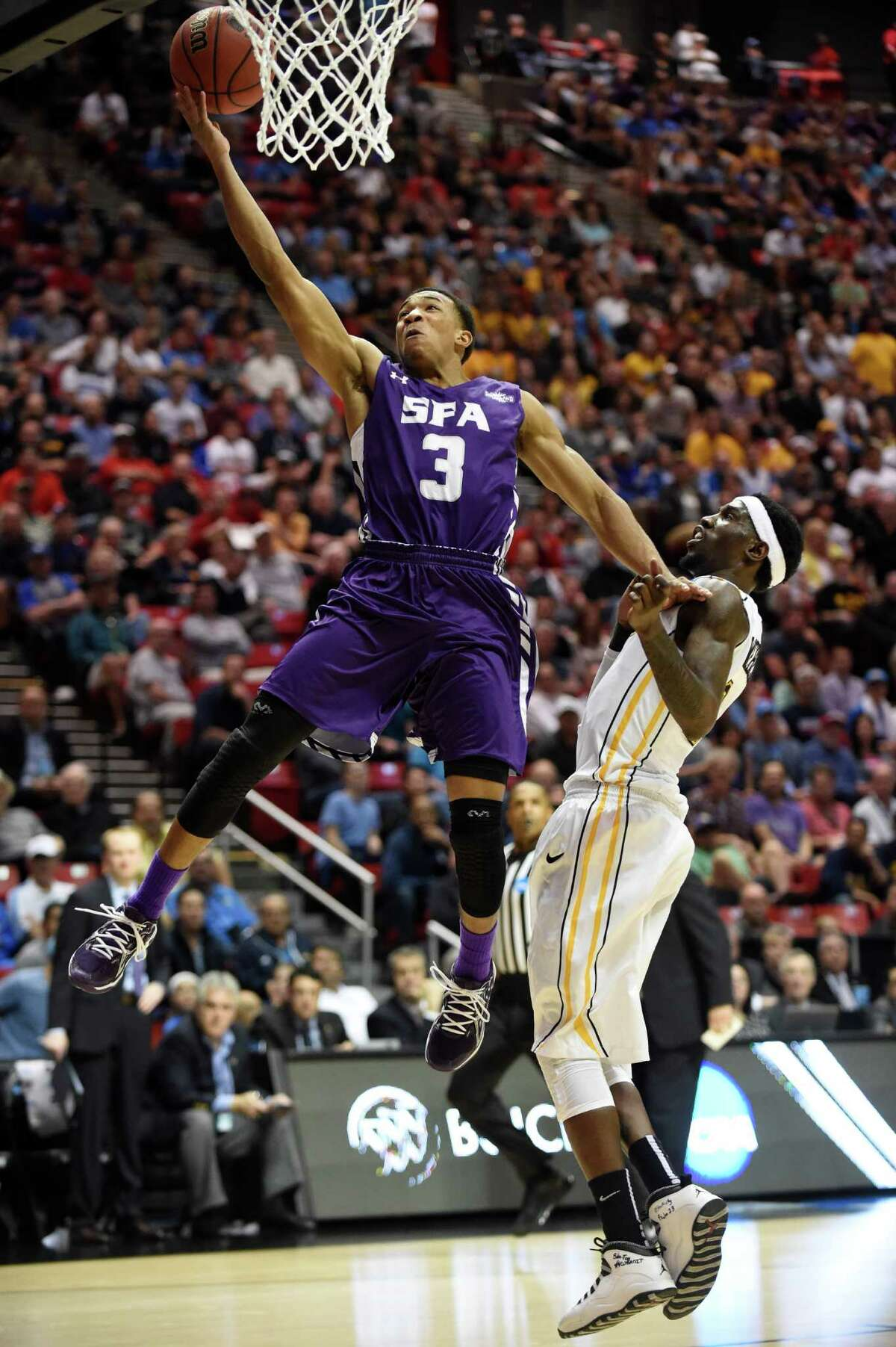 Stephen F. Austin guard Deshaunt Walker shoots past Virginia Commonwealth guard Briante Weber, right, during the first half of a second-round game in the NCAA college basketball tournament Friday, March 21, 2014, in San Diego. (AP Photo/Denis Poroy)