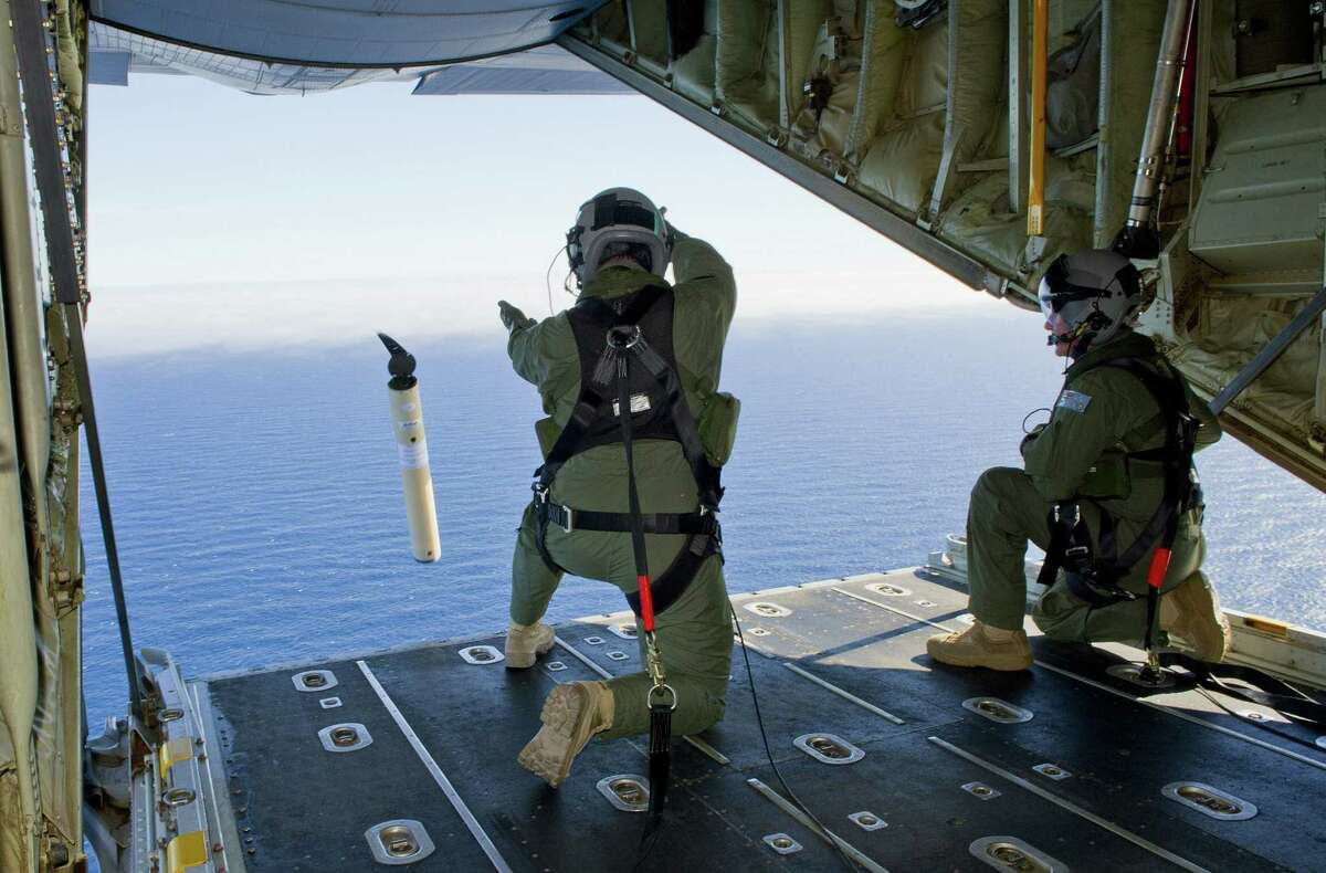 Australian air force loadmasters launch a self-locating data marker buoy into the southern Indian Ocean from a C-130J Hercules aircraft during the search for Flight MH370.