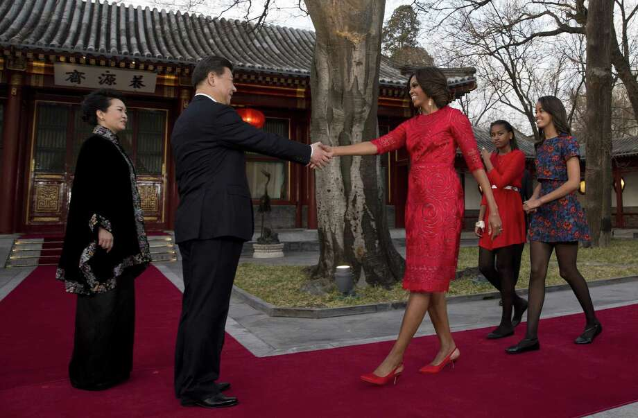 Michelle Obama, with Malia (right) and Sasha, greets Chinese President Xi Jinping and his wife, Peng Liyuan, in Beijing. Photo: Andy Wong / Associated Press / AP POOL