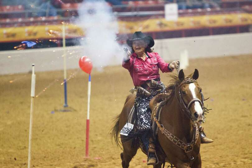 Collette Neuman competes on the cowboy mounted shooting at the Houston Livestock Show and Rodeo, Fri