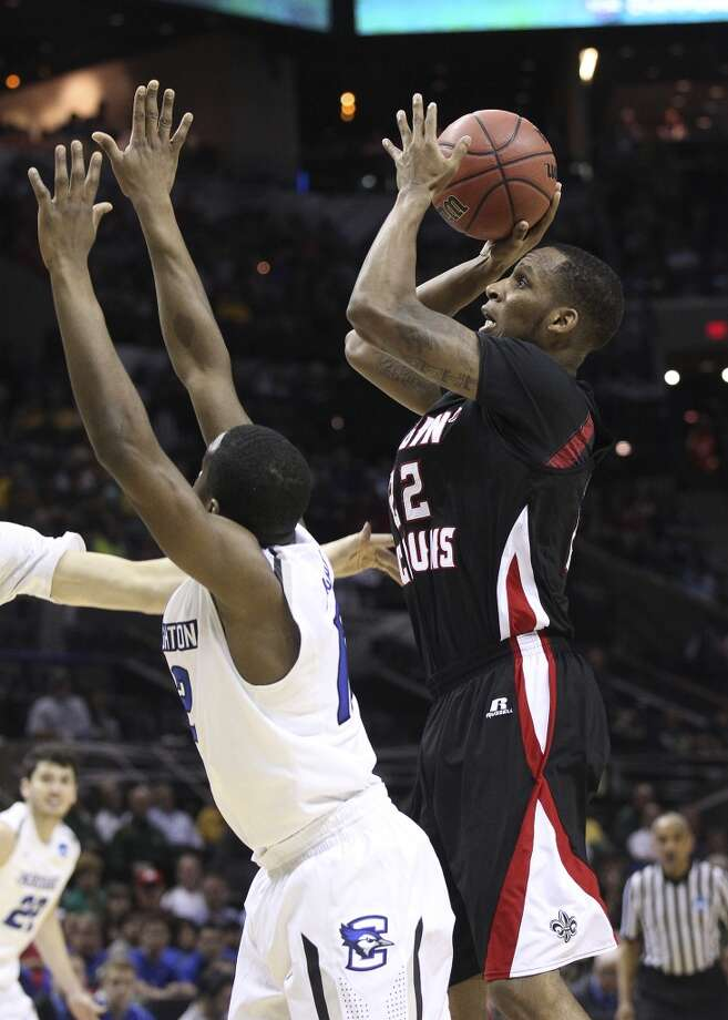 Lousiana-Lafayette's Elridge Moore (22) shoots over Creighton's Jahenns Manigat (12) in the first half of the second round of the 2014 NCAA Basketball Championship at the AT&T Center on Friday, March 21, 2014. Photo: Kin Man Hui, San Antonio Express-News