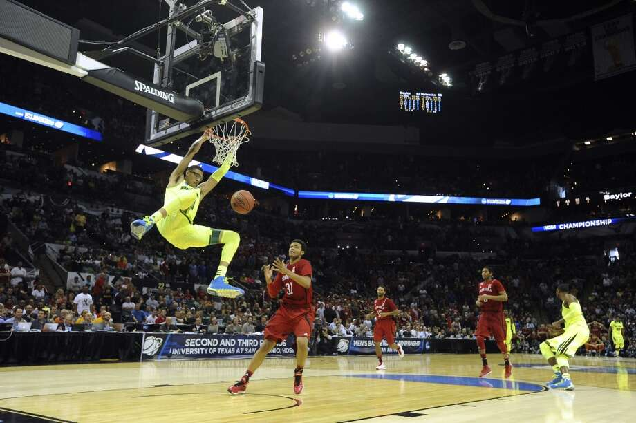 Baylor's Isaiah Austin (21) dunks as Nebraska's Shavon Shields (31) chases during second-round NCAA tournament second-half action in the AT&T Center on Friday, March 21, 2014. Photo: Billy Calzada, San Antonio Express-News