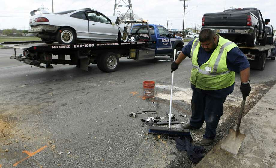Robert Mancha sweeps up debris from an accident on San Pedro near the Olmos Basin that left two men dead. Police said road rage was involved. Photo: Helen L. Montoya / San Antonio Express-News / ©2013 San Antonio Express-News