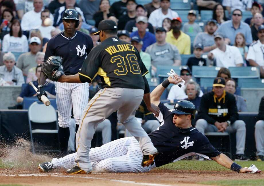 New York Yankees Mark Teixeira scores on a first-inning wild pitch thrown by Pittsburgh Pirates starting pitcher Edinson Volquez (36) in a spring exhibition baseball game in Tampa, Fla., Friday, March 21, 2014.  The Yankees Alfonso Soriano (12) watches from behind the plate. (AP Photo/Kathy Willens) ORG XMIT: FLKW115 Photo: Kathy Willens / AP