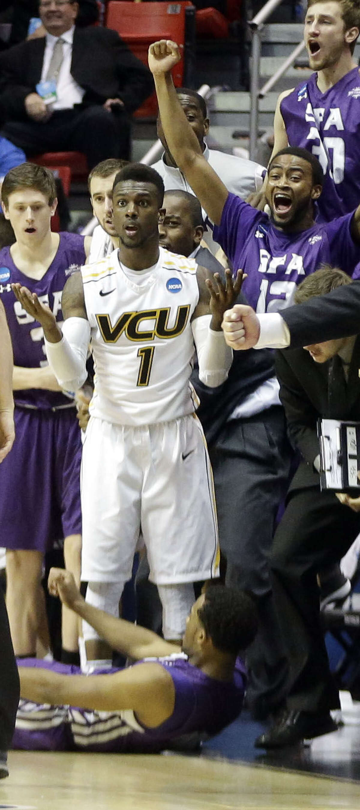 VCU's JeQuan Lewis stands in disbelief after fouling SFA's Desmond Haymon on a made 3-pointer late in regulation. The free throw forced OT.