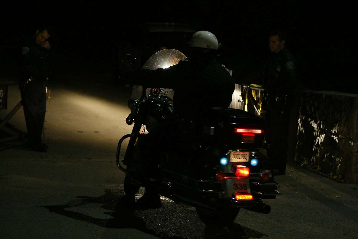 Officers let an officer on a motorcycle through a barrier at the edge of Bernal Heights Park on March 21, 2014 in San Francisco, Calif. An suspicious individual was reported in the park and after drawing a weapon was shot to death by police officers.