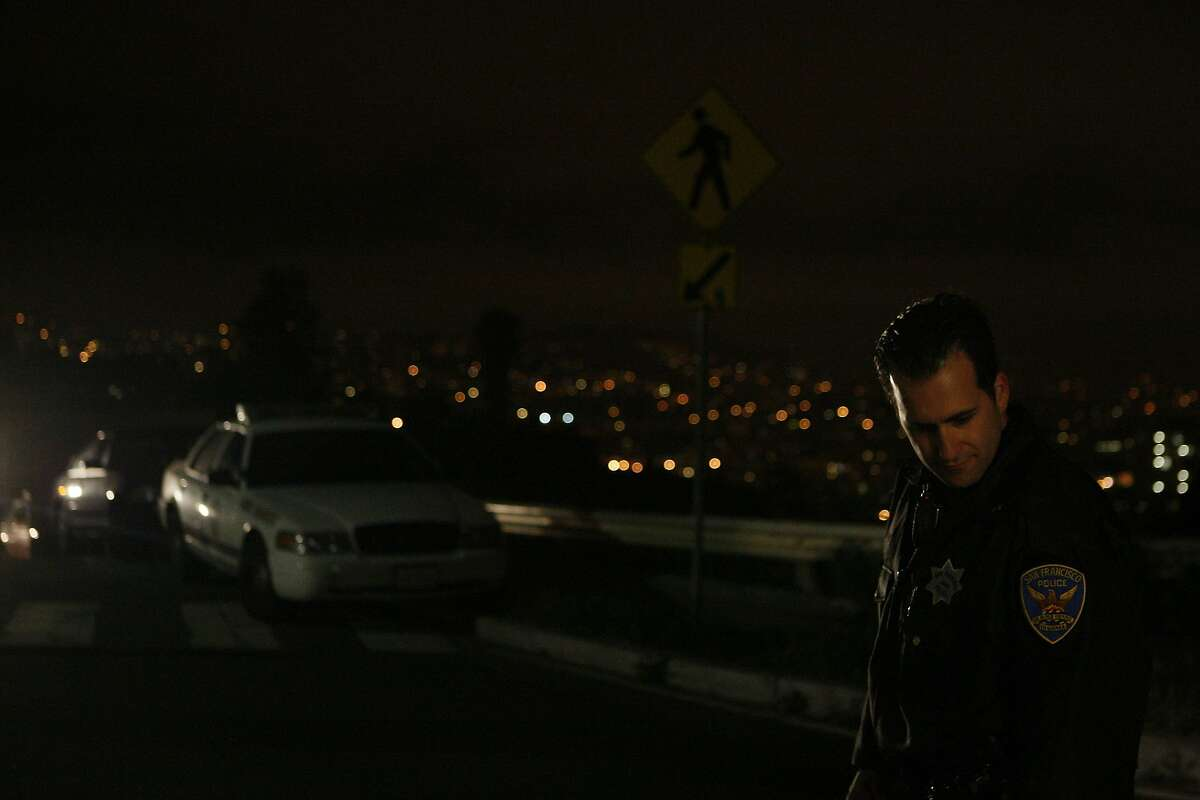 A San Francisco police officer waits to let a fire truck through at the edge of Bernal Heights Park on March 21, 2014 in San Francisco, Calif. An suspicious individual was reported in the park and after drawing a weapon was shot to death by police officers.