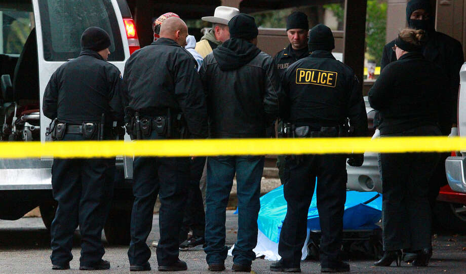Law enforcement and Bexar County medical examiner's personnel prepared to remove Cameron Redus' body from the scene of the December shooting. Photo: San Antonio Express-News / File Photo / ©San Antonio Express-News