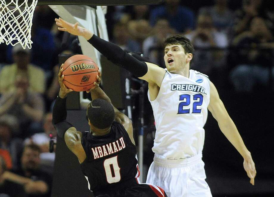 Lousiana-Lafayette's Bryant Mbamalu (00) has his shot blocked by Creighton's Avery Dingman (22) during second-round NCAA tournament first-half action in the AT&T Center on Friday, March 21, 2014. Photo: San Antonio Express-News / San Antonio Express-News