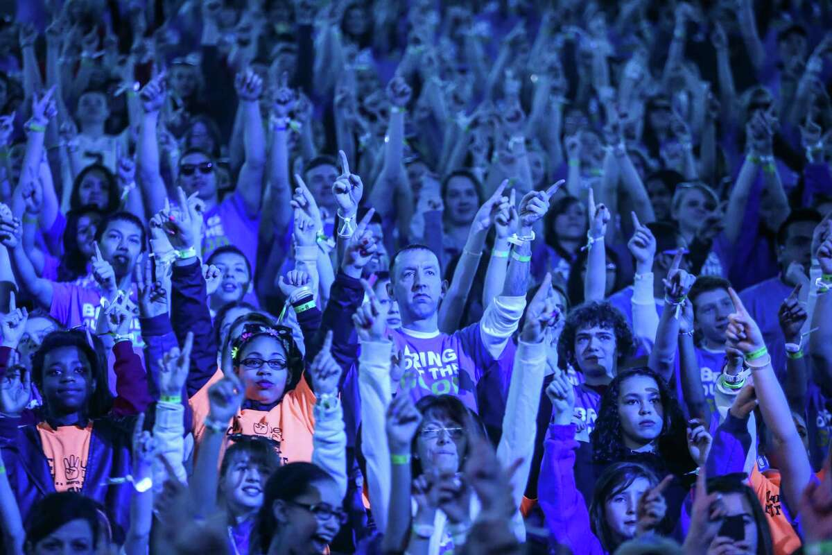 Participants raise their hands during We Day at KeyArena in Seattle. Thousands of young people came to the event. Spots were earned at We Day by students engaged in their communities. Photographed on Friday, March 21, 2014.