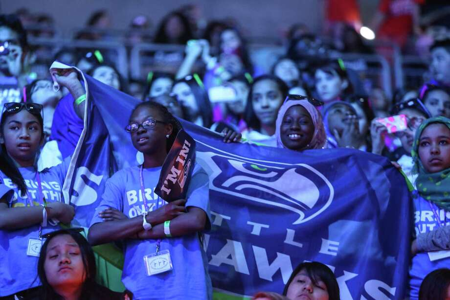 Participants hoist a Seahawks flag during We Day at KeyArena in Seattle. Thousands of young people came to the event. Spots were earned at We Day by students engaged in their communities. Photographed on Friday, March 21, 2014. Photo: JOSHUA TRUJILLO, SEATTLEPI.COM / SEATTLEPI.COM