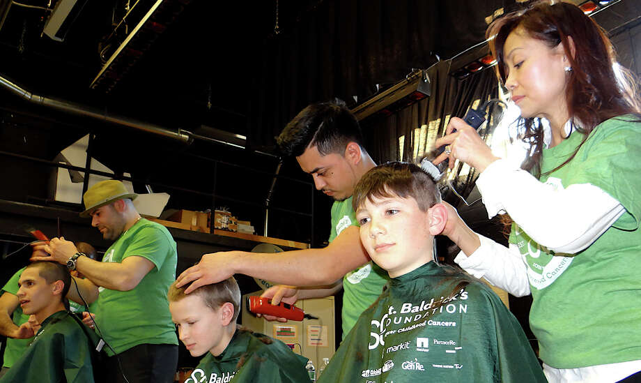 A trio gets their heads shaved at the St. Baldrick's fundraiser organized Friday by Team Teddy at Osborn Hill School. Photo: Mike Lauterborn / Fairfield Citizen
