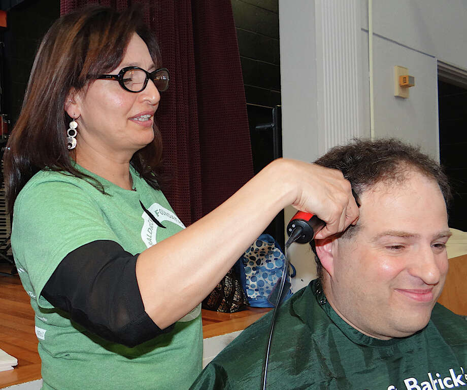 Ginger Thanasoulis shaves Bill Gerber's head at the Team Teddy St. Baldrick's head-shaving fundraiser for pediatric cancer research at Osborn Hill School on Friday. Photo: Mike Lauterborn / Fairfield Citizen