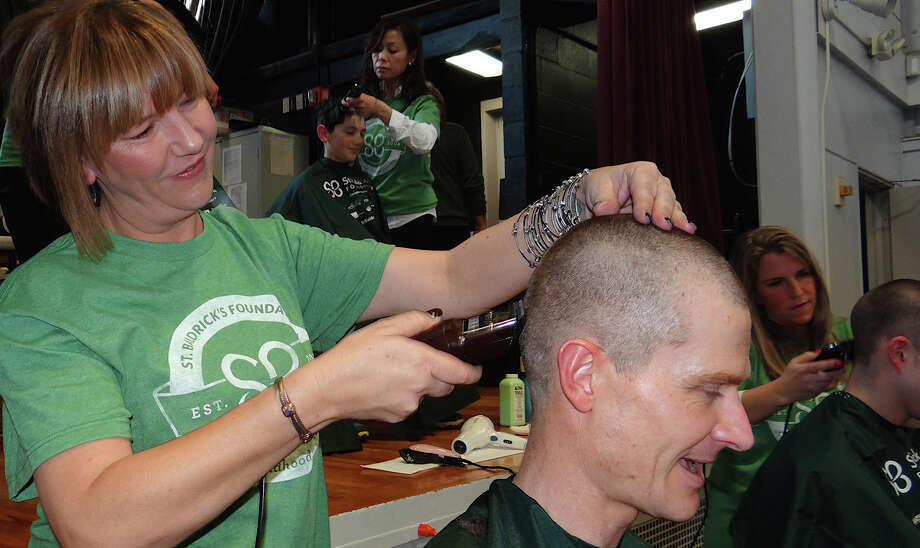 Robin Medina shaves Jim Muschett's head at the Team Teddy St. Baldrick's fundraiser. Photo: Mike Lauterborn / Fairfield Citizen