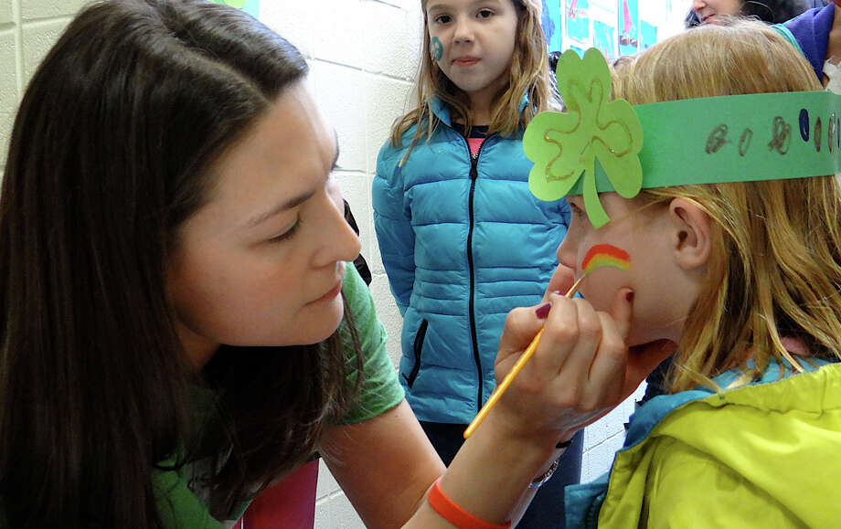 Kristin Golia paints a rainbow on 6-year-old Lily Dow's cheek at the Team Teddy St. Baldrick's head-shaving fundraiser Friday. Photo: Mike Lauterborn / Fairfield Citizen