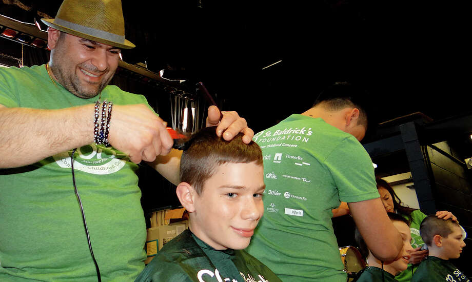 Mikail Tas shaves 13-year-old Finn Kery's head at the Team Teddy St. Baldrick's fundraiser for pediatric cancer at Osborn Hill School on Friday evening. Photo: Mike Lauterborn / Fairfield Citizen