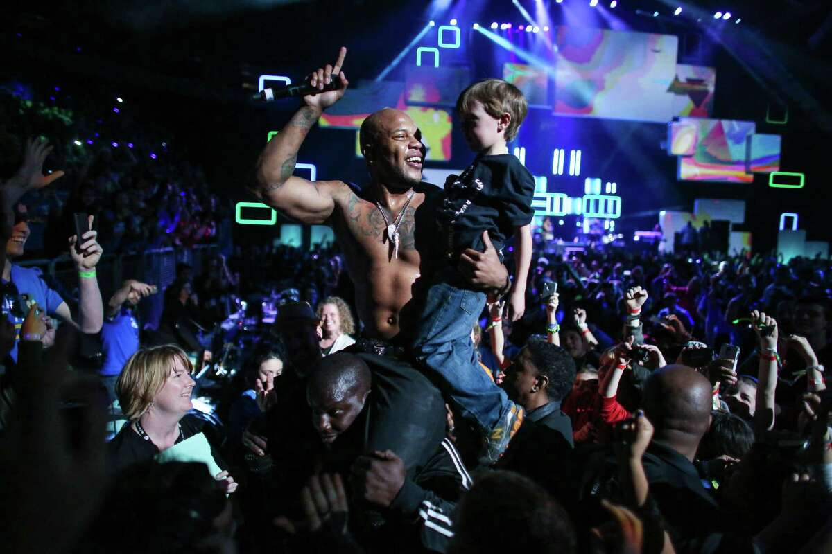 Recording artist Flo Rida hoists a young participant during We Day at KeyArena in Seattle. Thousands of young people came to the event. Spots were earned at We Day by students engaged in their communities. Photographed on Friday, March 21, 2014.