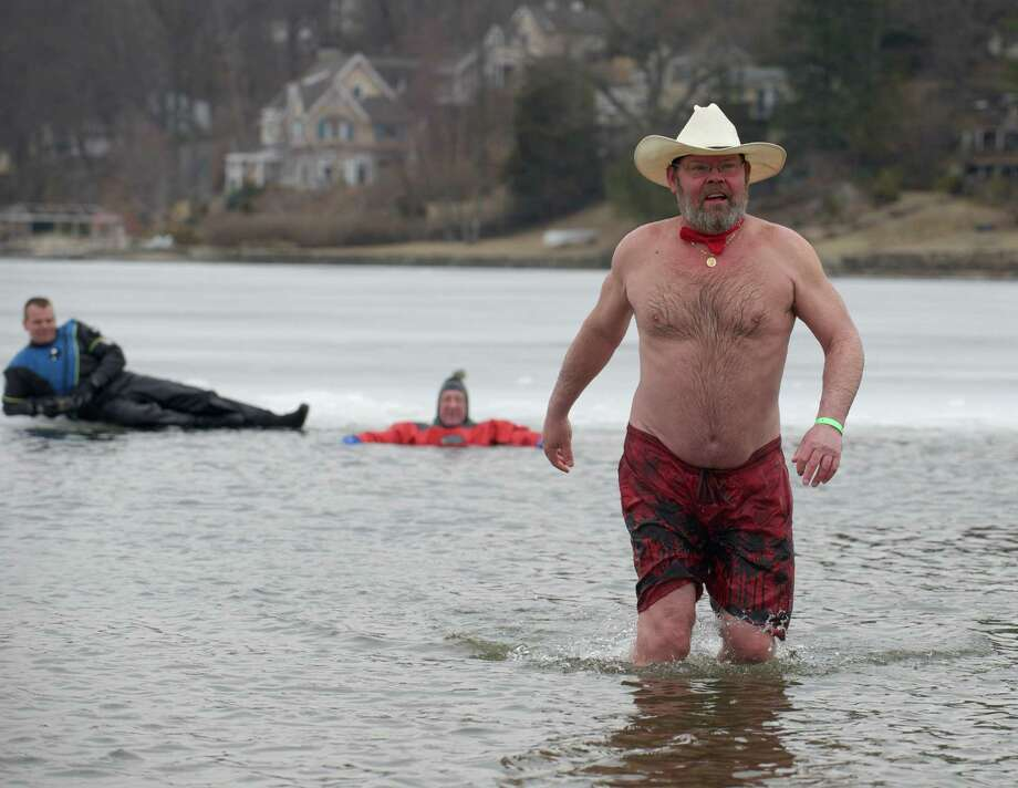 Andy Larsen, of Waterbury, walks out of Candlewood Lake on Saturday, March 22, 2014, as part of the Penguin Plunge, to raise money and awareness for the Special Olympics, at Candlewood Lake Park, Danbury, Conn. Behind him relaxing on the ice are Marcel Kruijs, from the Danbury Police Department Dive Team, left, and Walter Jablonski, of Watertown, a member of the Thomaston Regional Dive Team. Photo: H John Voorhees III / The News-Times Freelance